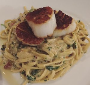Scallops & Linguine - Pan seared Scallops, overtop fresh linguine pasta, tossed in an herb cream sauce, artichokes, pancetta, and arugula.